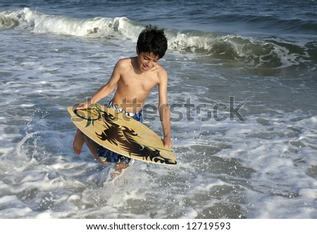 A young boy about to jump on a skim board.