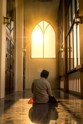 A young boy, an Asian Muslim, is praying in a mosque calmly, with sunlight shining from the front, creating an energetic atmosphere of faith.