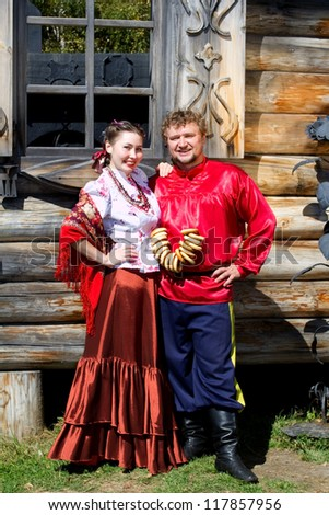 A young boy and a beautiful Russian girl in national costumes