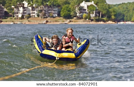 A young boy and girl riding a tube behind a boat.