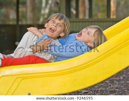 a young boy and girl who are brother and sister sit in the playground