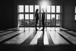A young boy and girl with long blond hair standing in front of the window. Black and white art monochrome photography.