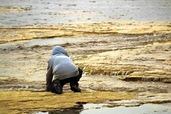 A young boy at a rivers edge watching water flowing