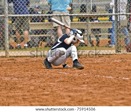 A young boy at bat ducking away from the ball as it comes close to his head.