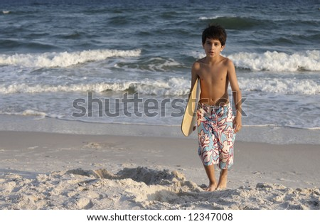 A young boy carrying a skim board.
