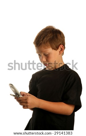 a young boy checks his cell phone as he is traveling with his suit case isolated on white with room for text
