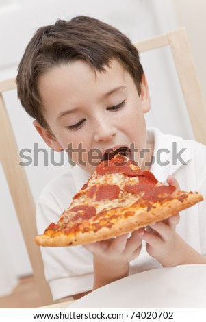 A young boy child eating a slice of pepperoni and cheese pizza