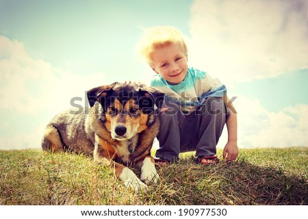 a young boy child is sitting outside in the grass, smiling as he pets his German Shepherd Dog.  VIntage Style Color.