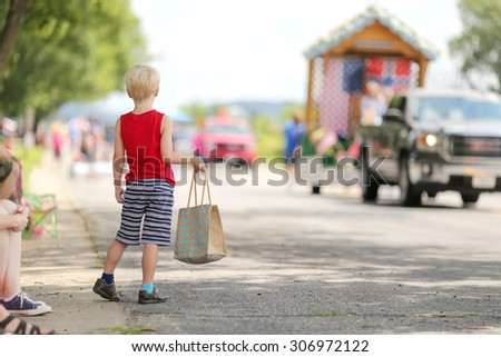 A young boy child standing outside in the summer watching a small town american parade and holding a candy bag.