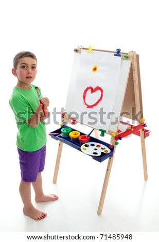 A young boy child stands by an easel with a beginning of a picture painted.  White background.