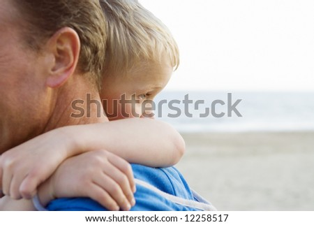A young boy cuddles his father.