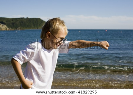 A young boy doing karate moves. Beach.
