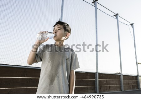 A young boy drinks water after a hard day of practice.