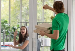 A young boy food delivery sender holding pizza paper boxes arrives at the customer's office and knocking the door to let her know while she working on a computer.