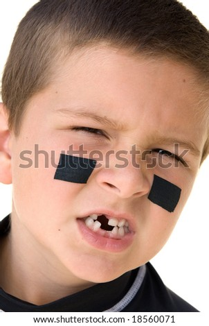 A young boy getting ready to play hockey snarls at the camera to show off his missing teeth.