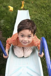 A young boy having fun at the top of the slide. Concept : Growth and development
