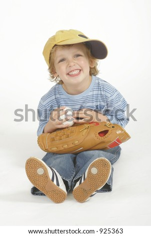 A young boy holding a baseball and wearing adult sized baseball cap and glove - studio shot in a portrait format