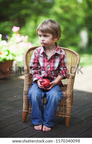 A young boy holding an apple sitting in a wicker chair