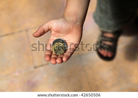 A young boy holding some Australian coins in his hand. Representing pocket money.