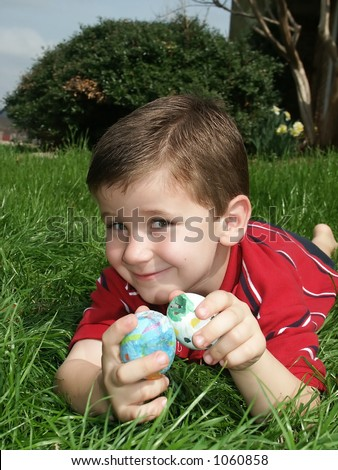 A young boy holding two Easter eggs.