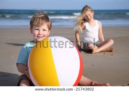A young boy holds a beach ball on the beach,  girl & ocean in the background.