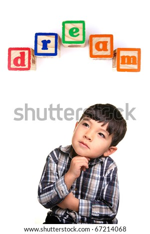 A young boy in a day dreaming pose under the word blocks.