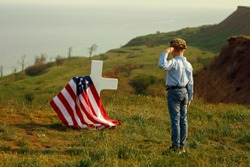 a young boy in a military cap salutes his father's grave on memorial day