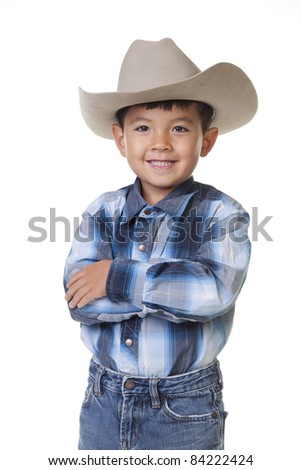 A young boy in cowboy clothes crosses his arms and shows a big smile.