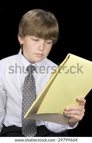 A young boy in formal business dress reads his notepad.  Image was shot against a black backdrop and can be used for any concepts and business inferences.