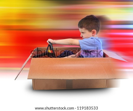 A young boy is driving in a cardboard box with red speed lines in the background. Use it for a shipping or imagination concept.
