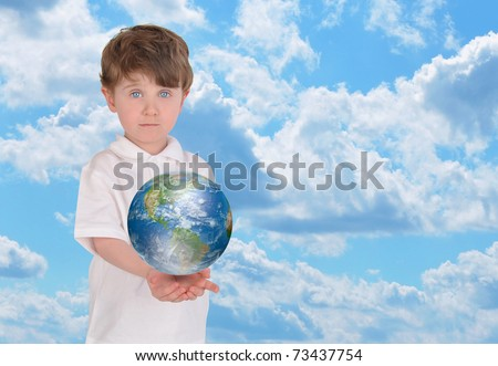 A young boy is holding the planet Earth in his hands and looks serious. There is a bright blue sky in the background and copyspace for text.