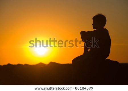 A young boy is sitting on a rock of a pier enjoying the sunset.