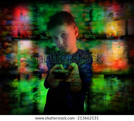 A young boy is watching a television screen pointing a remote control for a tv effect on children or concept.