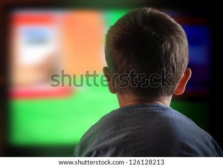 A young boy is watching a television screen with his back for a tv effect on children or a communication concept.
