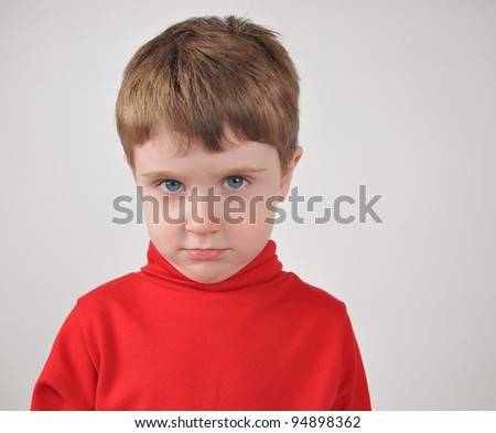 A young boy is wearing a red shirt and looks unhappy or upset.