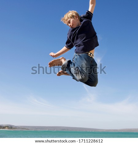 A young boy jumping in the air with excitement