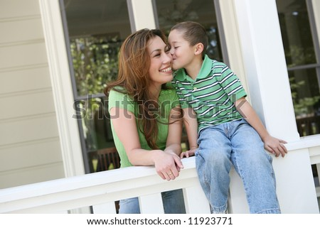 A young boy kissing his pretty mother on the cheek