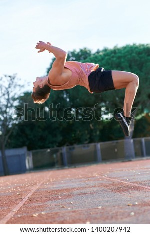 A young boy leaping somersault on the stadium. Copy space. Man athlete doing exercises outdoors. #1400207942