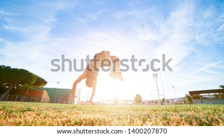 A young boy leaping somersault on the stadium with sun and blue sky on background. Copy space. Man athlete doing exercises outdoors. #1400207870