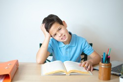 A young boy learning over his homework reading his workbook.