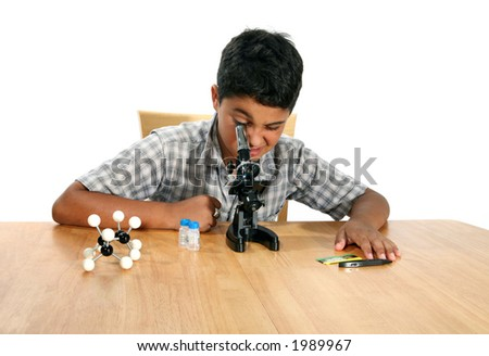 A young boy looking into a microscope