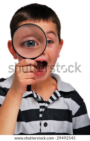 A young boy looking through a magnifying glass