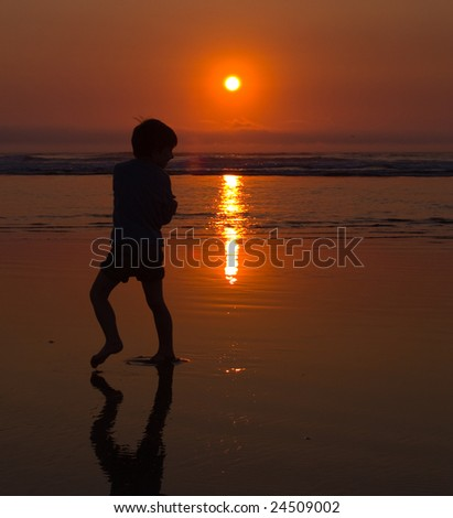 A young boy playing at the beach on the Oregon Coast at twilight.