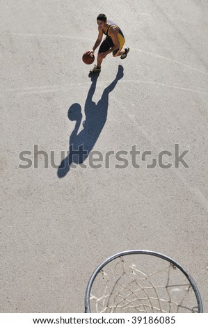 a young boy playing basketball outdoor on street with long shadows and bird view perspective
