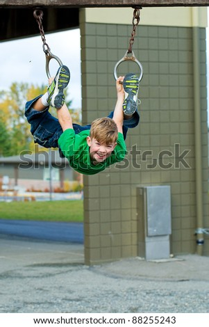 A young boy playing on a school playground.