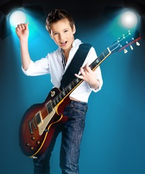 A young boy playing on the electric guitar on the stage with bright blue projector behind him