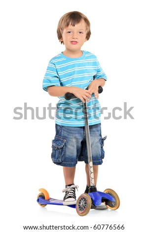 A young boy riding a scooter isolated against white background