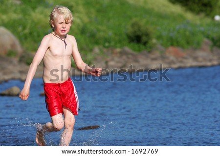 A young boy running in a lake, cooling off on a hot summerday