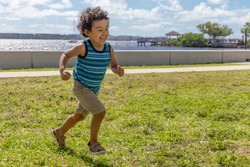 A young boy runs across the field while laughing out loud. The happy toddler is having a wonderful time running outdoors in the waterfront park.