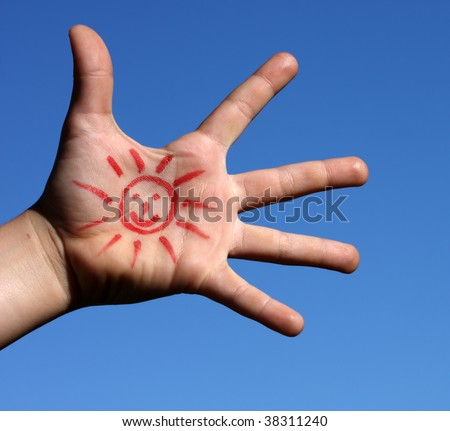 A young boy's hand with a drawing sun over a blue sky